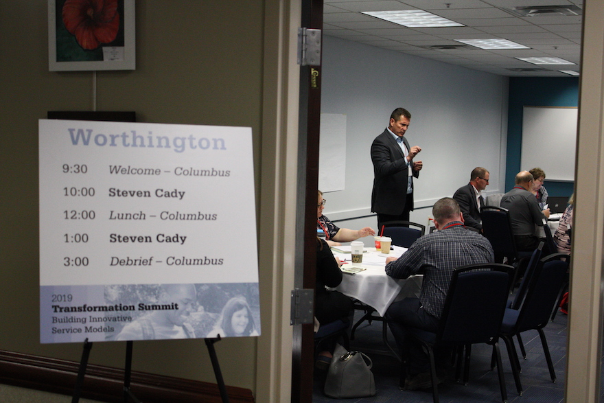 Worthington room schedule sign with Steve Cady in the background talking