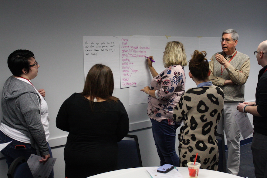 Group of attendees writing list on flip chart paper on the wall