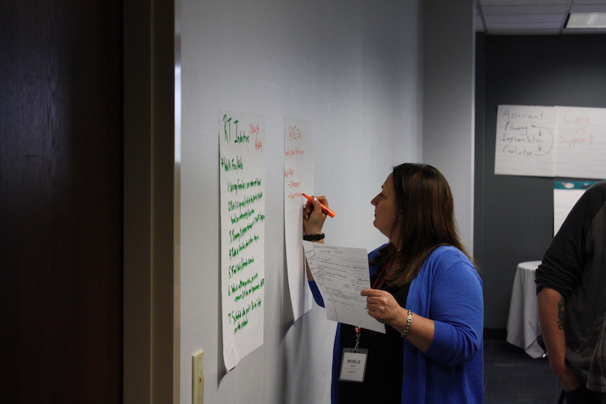 Attendee writing on a flipchart stuck to the wall focused