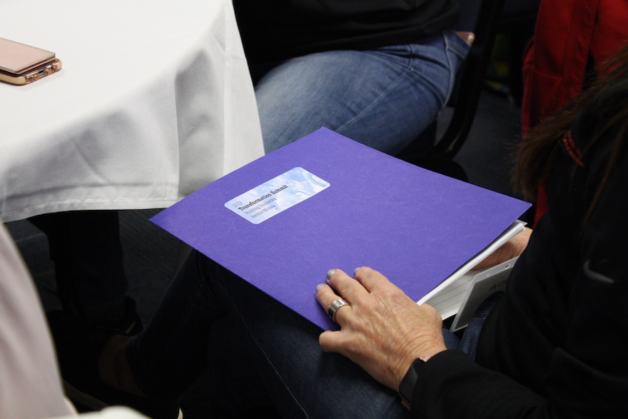 Attendee opening purple folder with Transition Summit 2019 label