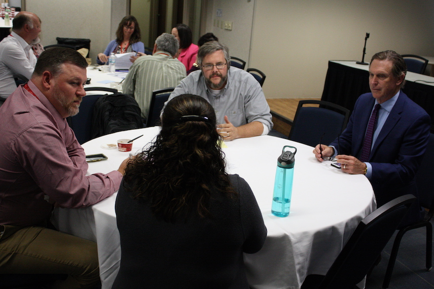Attendees talking with Director Davis at a round table during closing session